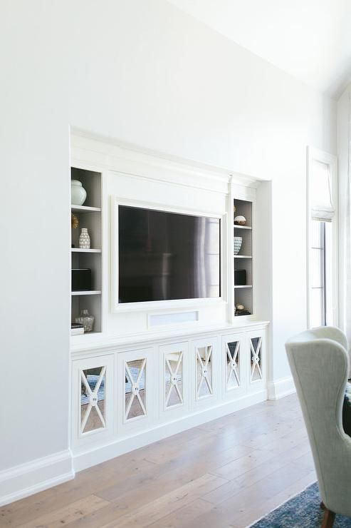 Chic living room nook is filled with a flat panel tv niche flanked by shelving as well as mirrored x front cabinets.