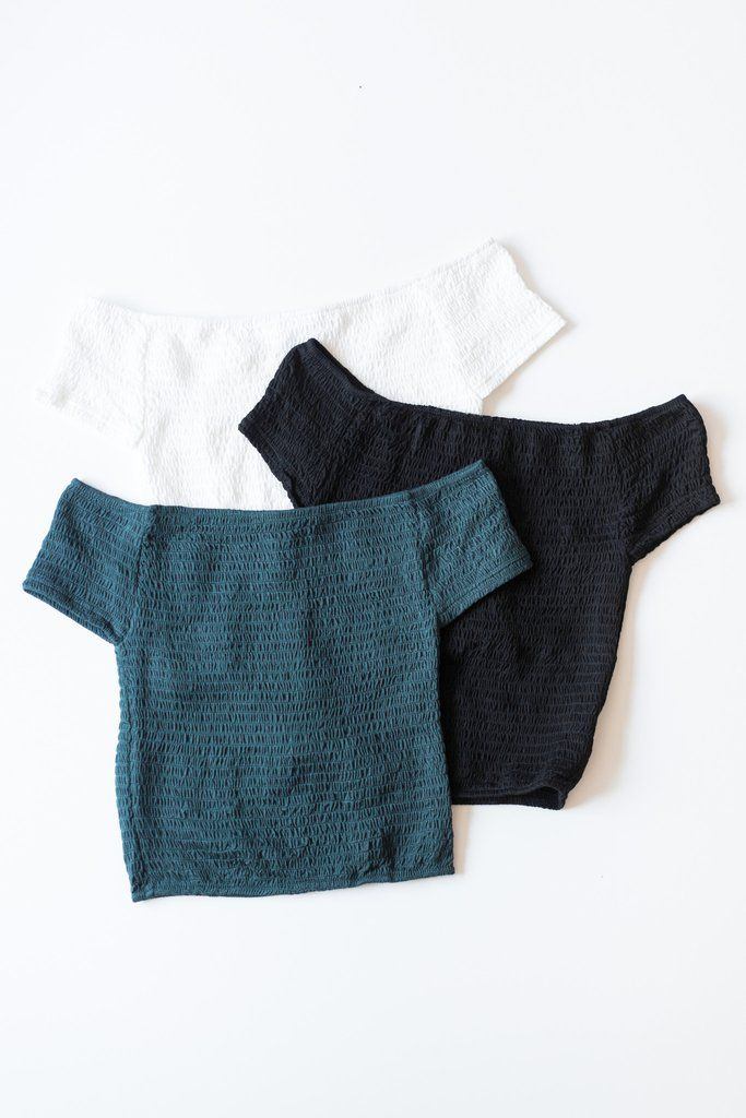 Stretchy off-shoulder crop top made with smocked jersey knit fabric. Size small total length measures approx. 13. Available in Teal, Black, or White. 95% Rayon