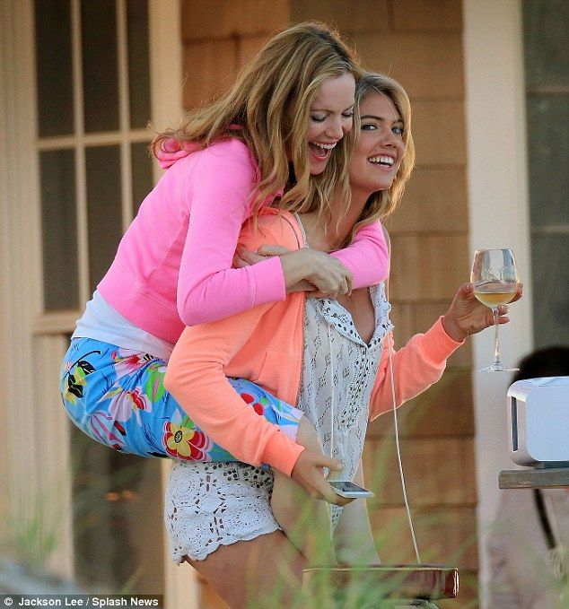 Enjoying a tipple: The model Kate Upton held a chilled glass of white wine as Leslie Mann jumped on her back for a piggyback ride