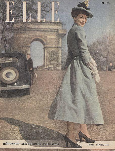 1 hình ảnh bìa đẹp của tạp chí Elle, cô gái trong trang phục thời trang và hợp mốt của những năm 40s với vest đầm dài đến  gần mắt cá chân, màu sắc xanh bạc hà trang nhã, kết hợp với mũ đội lệch cùng tông màu váy có gắn hoa trang trí , găng tay  trắng và giày oxford. Cô gái để tóc ngắn cá tính và trang điểm nhẹ nhàng.