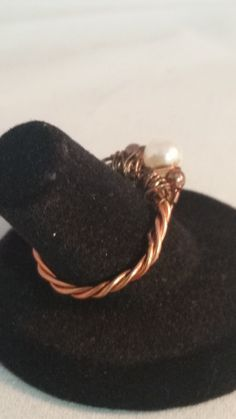 A single pearl flanked by copper beads are the crown of this unique ring. Intertwined copper wires form the band.