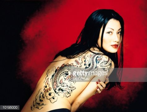 Stockfoto : Woman with dragon tattoo on back