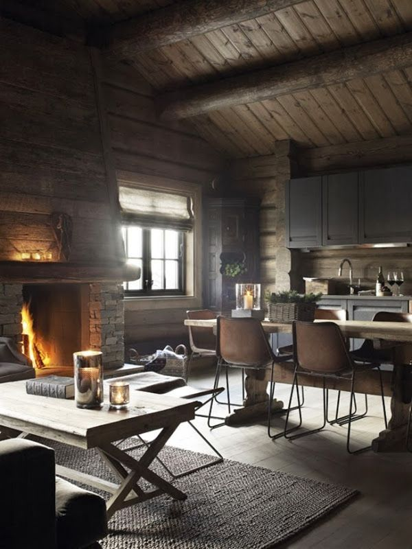Rustic cabin with open kitchen, living room and dining creates a  comfortable space for conversations near the fire.