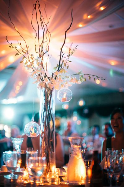 Pretty wedding centerpiece using a cylinder vase and branches.