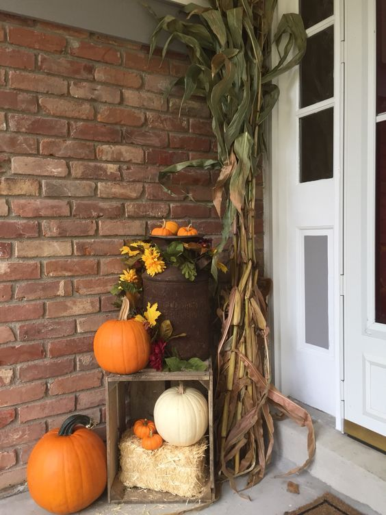 a porch dressed for fall with an old milk can, corn stalks and a crate