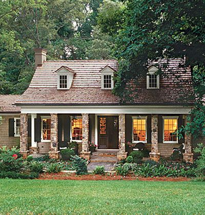 brick columns flank the front of the remodeled home with large windows with black shutters and window dormers open up the shingle roof