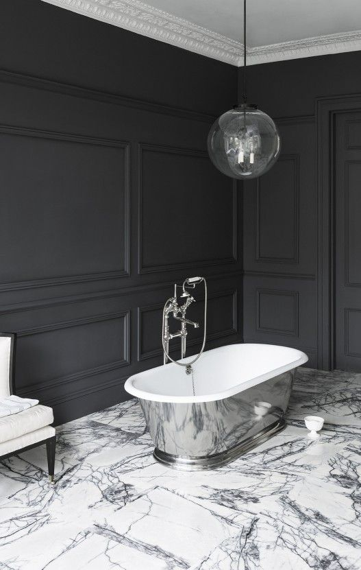 Monochrome bathroom with marble flooring, chrome freestanding bathtub and dark grey wooden panelling painted in Perse by Paint and Paper Library