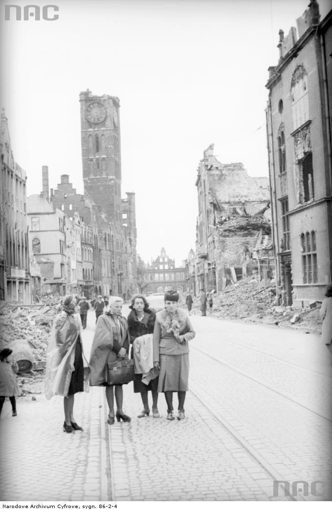 Grupa kobiet na ul. Długiej - 1. z lewej Aniela Witkowska, 3. z lewej Felicja Witkowska. W tle budynek Ratusza Głównego Miasta z uszkodzoną wieżą oraz w tle ruiny Zielonej Bramy.