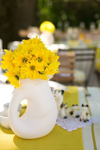 Bright yellow daisy poms, clustered together, make for great DIY arrangements. The unique containers and figurines add a fun twist. Shop Daisy Poms and other wedding flowers at GrowersBox.com