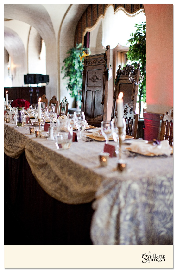 "A traditional head table was used for the reception, but with the addition of ""king"" and ""queen"" chairs. Taper candles in brass candleholders, along with votives were spread out down the length of the table, covered with an ivory lace overlay. (Photo credit: Svetalana Yanova)"