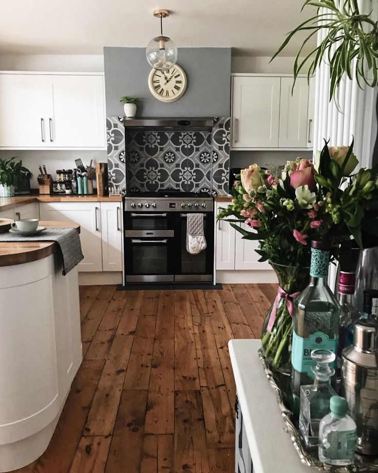 Tiled splashback, wooden floorboards, white kitchen units