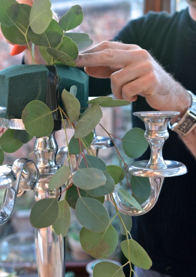 Step one: Begin by taping the floral foam to the top of the candelabra and start to build the outline of the arrangement with foliage, ensuring some of it is cascading down over the arms of the candelabra