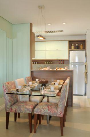 A cozinha deste apartamento em Campinas (SP) é separada da sala por uma bancada de MDF laqueado branco com tampo de granito. A divisória também abriga armários. Duas cadeiras brancas se contrapõem às outras floridas. Projeto da arquiteta Rosely Pardini Gallo Rech.
