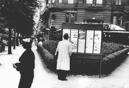 "A pedestrian stops to read an issue of the antisemitic newspaper ""Der Stermer"" (The Attacker) in a Berlin display box. ""Der Stermer"" was advertised in showcase displays near places such as bus stops, busy streets, parks, and factory canteens throughout Germany. Berlin, Germany, probably 1930s."