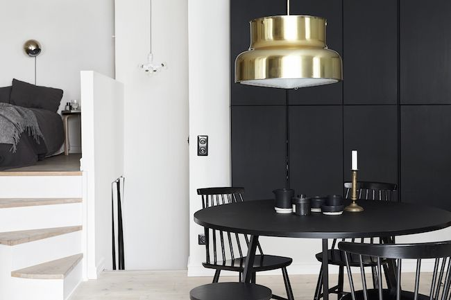 A black statement wall adds impact to thistwo-story studio, while an oversizedgoldpendantbrings dimension to the space.
