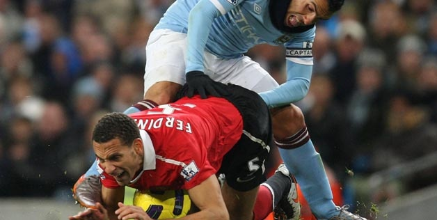 Does not look like a fun position to be in...for either of them!  Rio Ferdinand of Manchester United clashes with Carlos Tevez of Manchester City on Nov. 10, 2010 (© Matthew Peters/Man Utd via Getty Images)