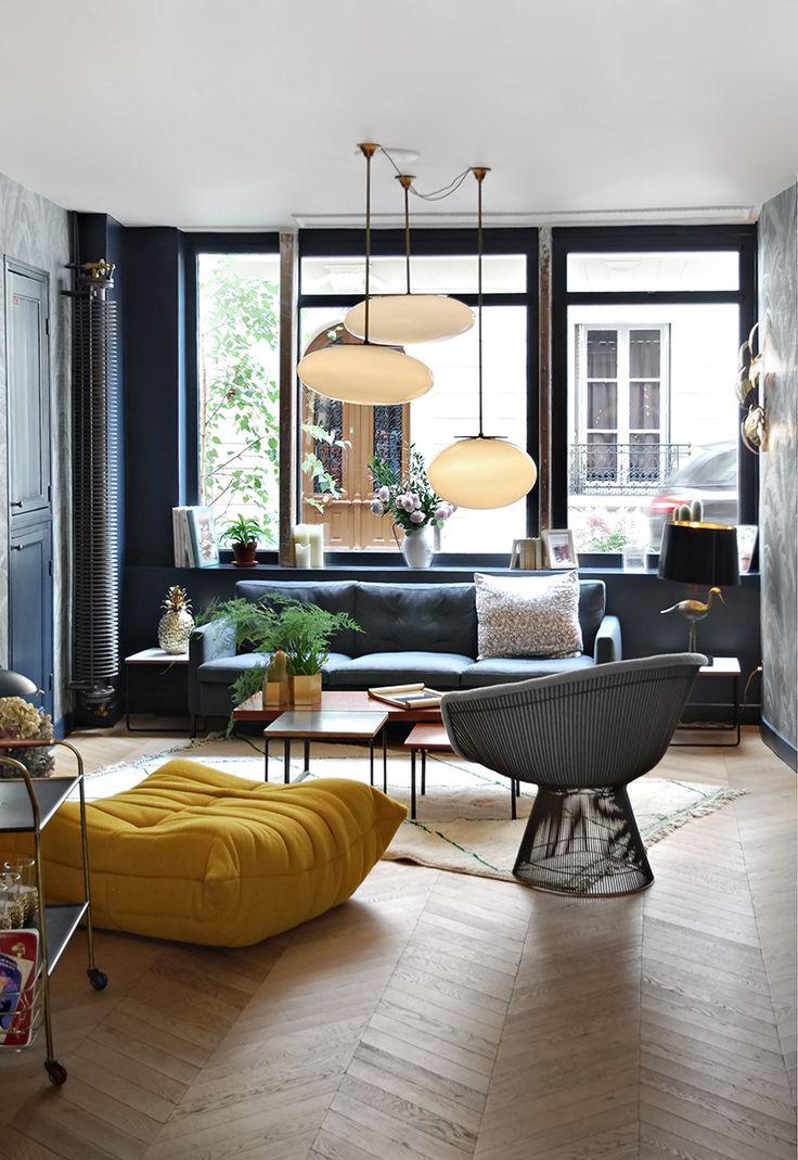 Espaço cinza com um toque amarelo. Aposte em pendentes delicados e puffs para um espaço leve e jovial.