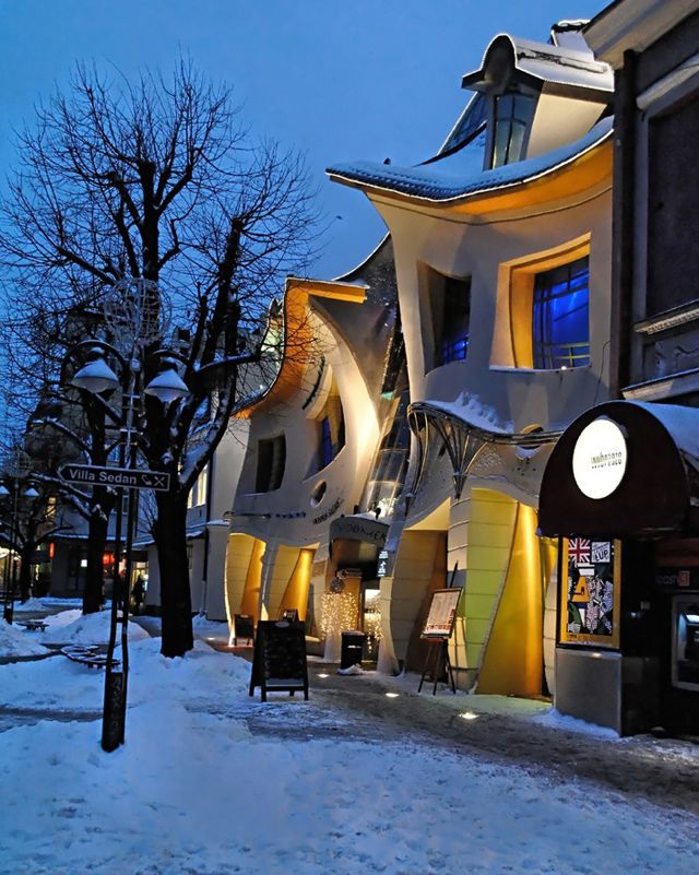 """Krzywy Domek (""""Crooked House"""" in English) is a unique shopping center in Sopot, Poland designed in 2004 by the architecture firm Szotynscy & Zaleski. The building's crazy lines make it look more like a cartoon fun house than a shopping center. According to Wikipedia, Szotynscy & Zaleski were inspired by the fairytale illustrations of Jan Marcin Szancer and Per Dahlberg."""