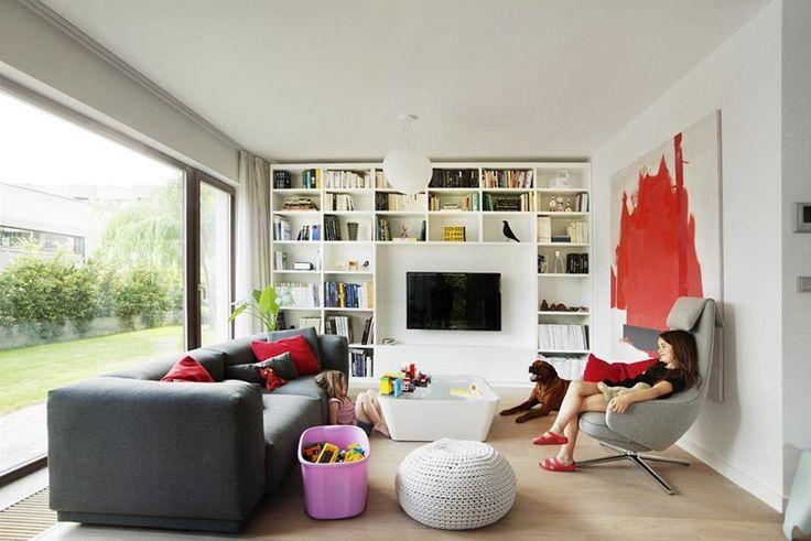 Obývací pokoj je zařízen v neutrálních barvách. Pohodlná tmavě šedá pohovka je doplněna zajímavým designovým křeslem. Bílá asymetrická kniho...