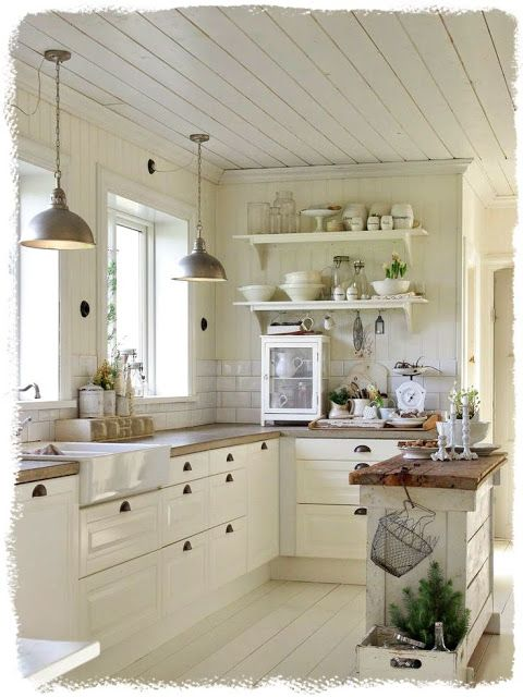 gorgeous kitchen with planked walls & ceiling, butcher block counters, white cabinets with cup pulls and industrial lighting.