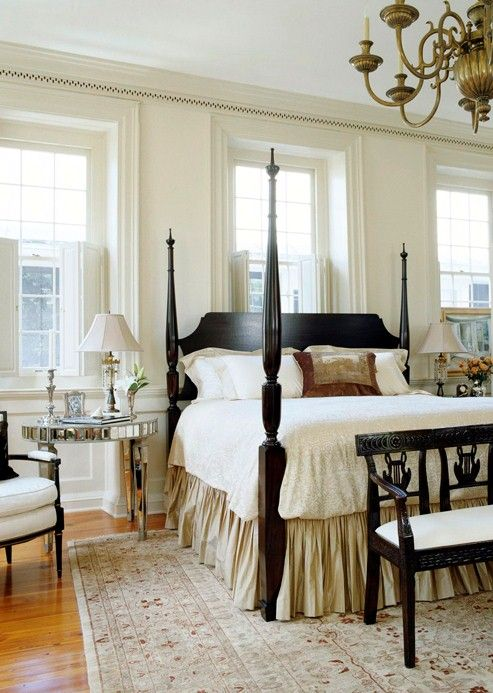 An abundance of natural light, which tumbles in from windows gracing three sides of the room, helps this master bedroom feel larger than its actual footprint. White walls and a largely neutral color palette also add to the voluminous feeling.