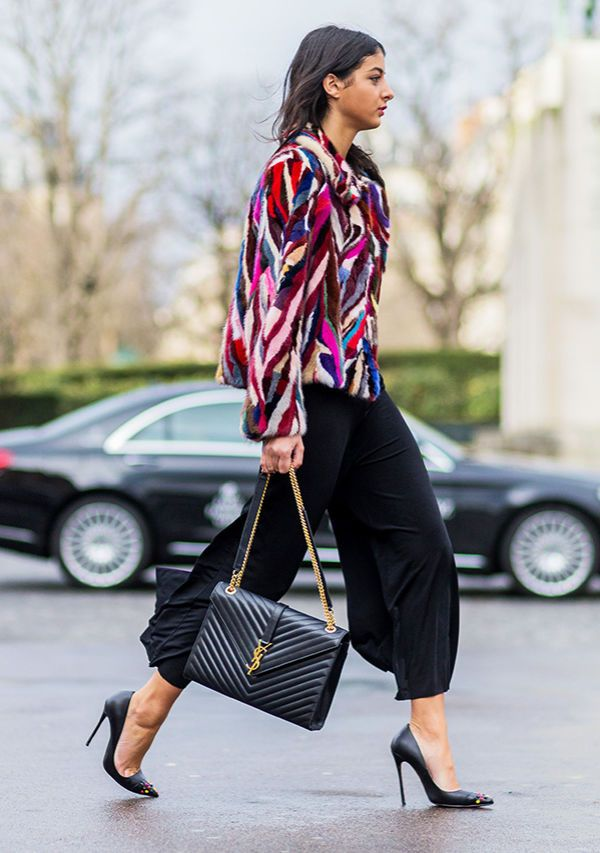 A multicolored striped jacket is worn with black culottes, pointed toe pumps, and a YSL bag
