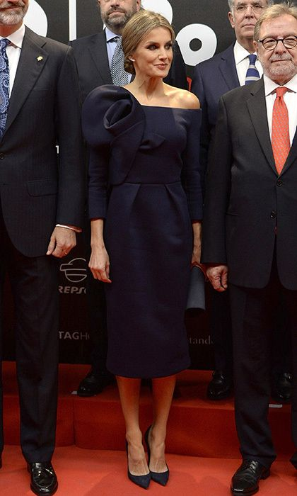 Queen Letizia of Spain wore designer Delpozo for the first time, choosing a dark blue off-the-shoulder look for the As sports newspaper 50th anniversary dinner at the Palacio de Cibeles in Madrid on December 4. The tailored dress, which the royal wore with matching heels, featured an architectural oversized rose detail on one shoulder. Photo: © Fotonoticias/Getty Images