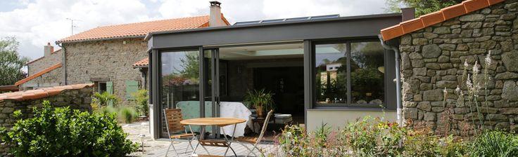 extanxia, véranda concept alu, vue extérieur avec mur en pierre et véranda en angle et puits de lumière avec terrasse