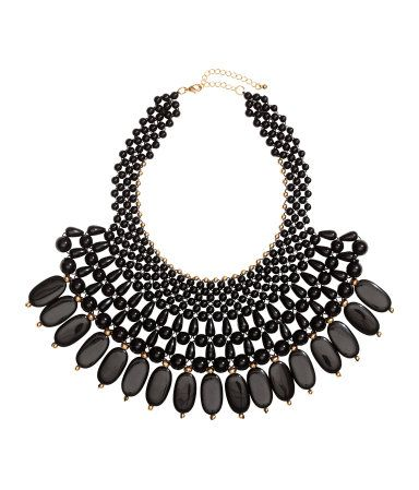 Black bib necklace with plastic beads and pendants. Adjustable length. | H&M Accessories