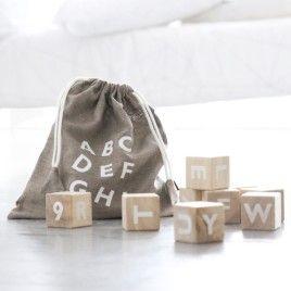 Träklossar med bokstäver i linnesäck