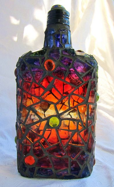Bottle painted with glass paint, mosaiced in clear glass and grouted in dark gray.