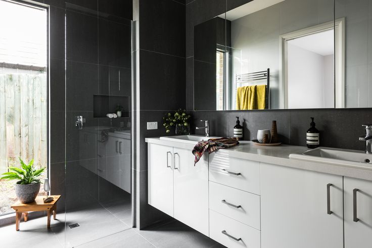 White cabinetry contrasts beautifully against the dark grey tiles