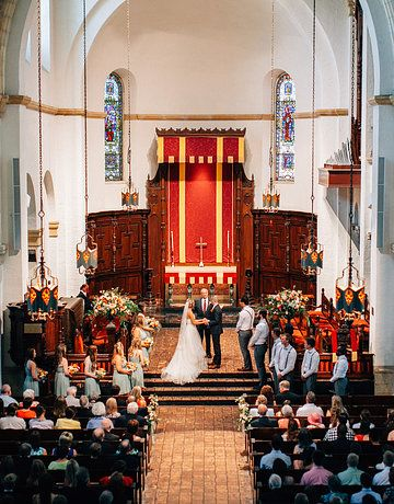 wedding in a  historic chapel, the altar is flanked with urns filled with loosely arranged greenery, cream, peach and orange flowers.