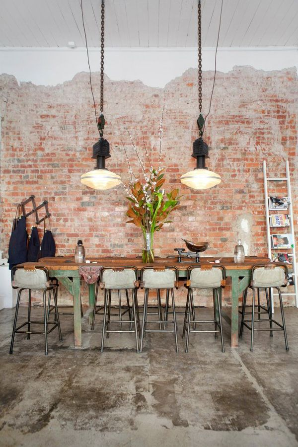 Industrial stools in pale green, factory lighting, concrete floor and exposed brick wall