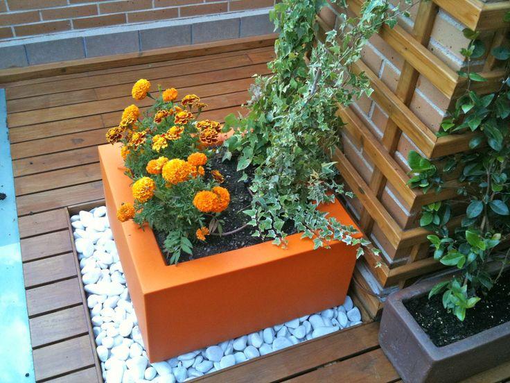 atractiva jardinera naranja sobre guijarros blancos con tagetes del mismo color