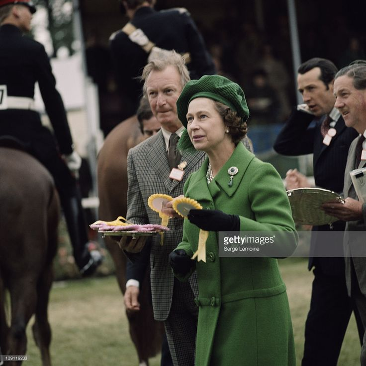 Queen Elizabeth II Wearing A Green Coat And Matching Hat Awards Rosettes At The