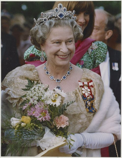 Queen Elizabeth II, resplendent in cape, jewels, royal insignia...and a floral bouquet