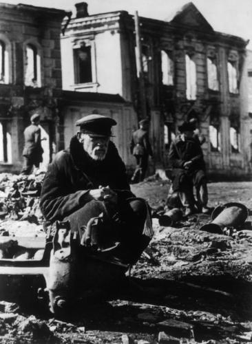 Suffering Population: A Russian squats in the ruins after an attack on his home town of Rzhev.