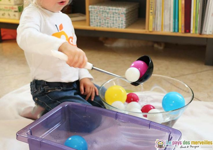 Transvaser des balles avec une louche : un jeu d'eau Montessori parfait pour travailler la motricité et la patience des enfants dès 18 mois.