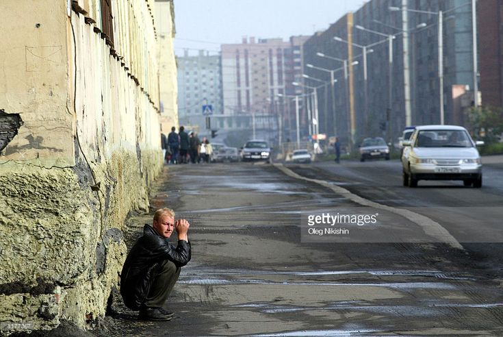 A man sits on the street in Norilsk, July 22,2002. A Nickel plant stands on one side of the town and a Copper refinery on the other. The off-gases from both create a semi-permanent haze of sulphur dioxide in the streets of the town.