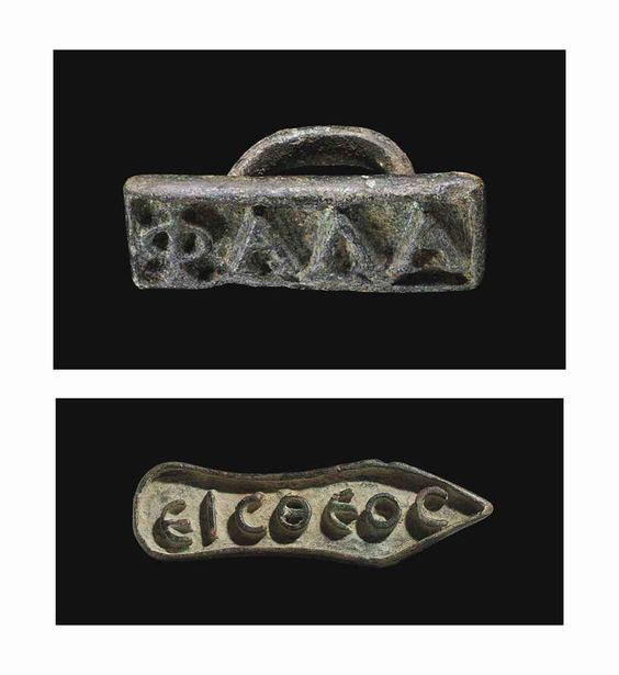 "Two byzantine bronze bread stamps, 4th-7th century A.D. One rectangular in form, with a Greek inscription in relief KALAFk, likely an abbreviation of the name Alafos, with a ring handle at the back and one in the form of a silhouette of a shoe, with the Greek inscription in relief, EICTHEOC, on the underside, reading ""One God"" Shoe-shaped, 12.4 cm long max. Private collection"