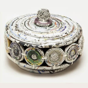 This lidded bowl was handcrafted by artisans working with the Women's Multipurpose Cooperative in Baguio City, the Philippines. Using an innovative process, the women turn old newspapers into new and beautiful products by wrapping the paper into coils and forming them into spiraled building blocks.