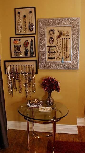 Plusieurs cadres disposés au mur. Des fonds en tissus et des poignées, crochets pour accrocher les bijoux.