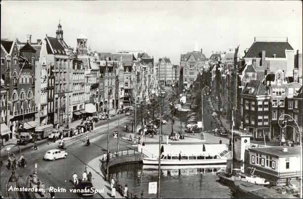 1950's. View on the Rokin in Amsterdam seen from Spui. Rokin is a major street in the center of Amsterdam. Originally it was part of the river Amstel. The Rokin begins at Muntplein square and ends at Dam Square. In 1936, the part between Spui Square and Dam Square was filled in. On the remaining part of the water, canal boats are now moored. Photo Van Leer's Fotodrukindustrie N.V. #amsterdam #1950 #Rokin