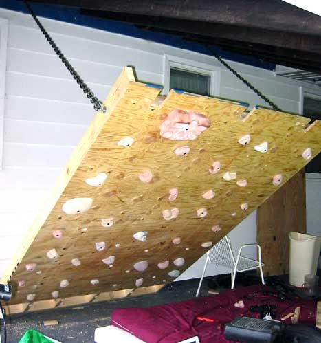 Cool idea for a home climbing wall using cut outs to leave space for rafters and chains to adjust angle.