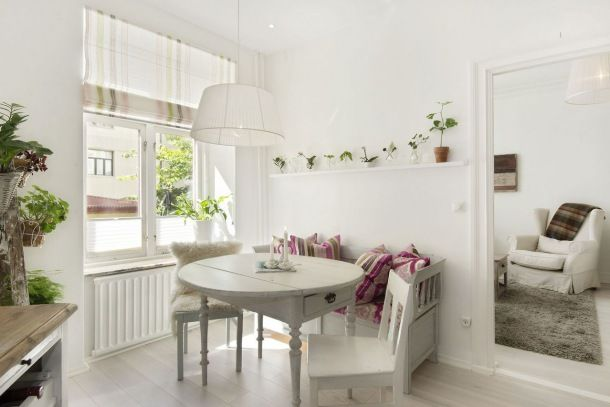 drewniana ławka skandynawska,okrągły rozkładany stół z krzesłami i roleta rzymska w paski biało-różowo-zielone na oknie w jadalni