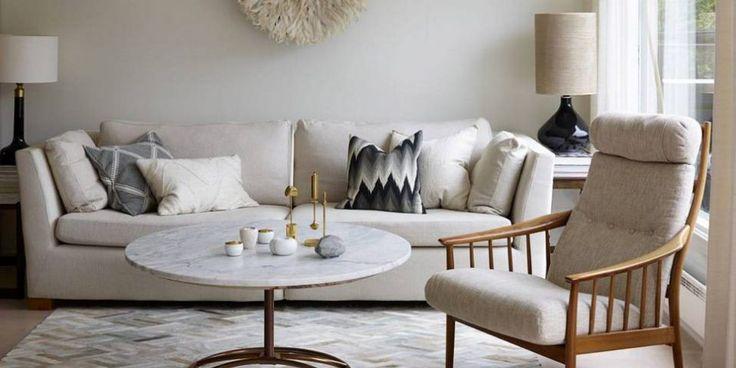 LYSE NYANSER: Stuebordet er laget av understellet fra et gammelt bord og en ny marmorplate fra Mina Milanda. Lenestolen er kjøpt brukt, og hadde opprinnelig mørkegrønt, storblomstret trekk. Sofa fra Ikea med svartmønstret pute fra Milla Boutique. og bak t.h. en linpute fra Bolina. Veggdekorasjonen i fjær er en afrikansk hatt fra Anouska. Lampe t.h. fra Eske og lampe t.v. et bruktfunn. Teppe fra Zara Home. Hvite telysholdere og diamantformet dekorasjonsstein, alt fra Milla Boutique. © FOTO…