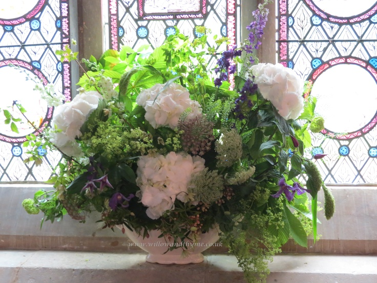 Hydrangeas, ammi, larkspur, viburnum, clematis and a mix of country flowers.
