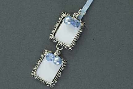 Double Photo Frame Wedding Charm The Double Photo Frame wedding charm is a pretty way to remember loved ones at your wedding by placing their photos into each frame and attaching it to your bouquet. Each charm is embellished with pretty pearl and crystal bead dangles. The charm is presented in a pretty organza drawstring bag. Available in gold or silver and a fabulous range of bead and ribbon colours.