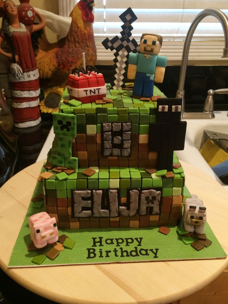 """Minecraft birthday cake. Includes: sword (made from gum paste), TNT, Steve, Creeper, Enderman, the pig and the wolf (all made from fondant). Took about 800 1x1 cm fondant squares. The cake was an 8"""" base and 6"""" top, both about 3"""" tall. The name was cut with basic letter cutters (from Hobby Lobby) and I added dents with a veiner too then topped with silver lustre dust. """"Happy birthday"""" was from tappets. TNT has a birthday candle sparkler in center (from Party City)."""